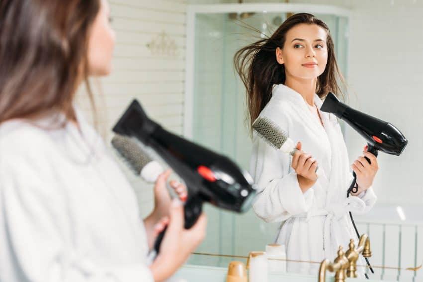 Imagem de mulher secando o cabelo com escova na mão em frente ao espelho.