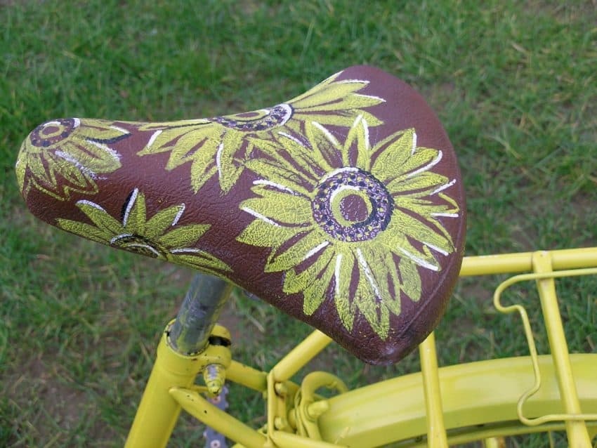 Selim de bicicleta amarela estampado com flores.