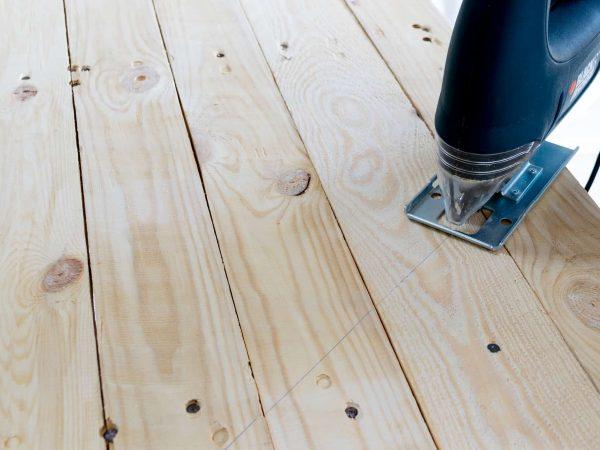 Uma serra tico-tico sendo utilizada sobre uma superfície de madeira com risco indicando a linha de corte.
