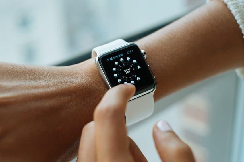 Imagem de uma mulher mexendo em seu smartwatch branco no seu pulso.