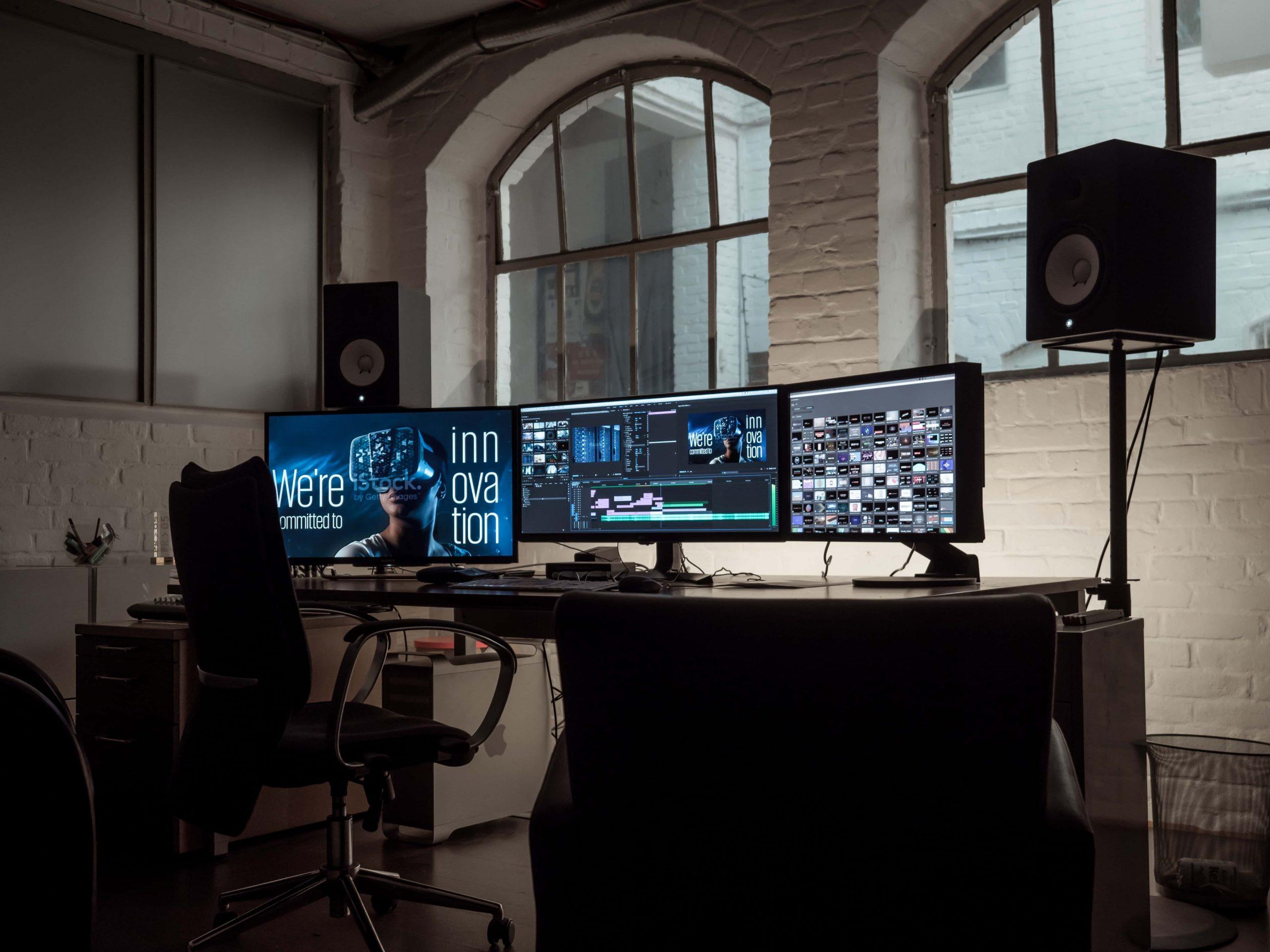 Imagem mostra três monitores em suportes em cima de uma mesa.