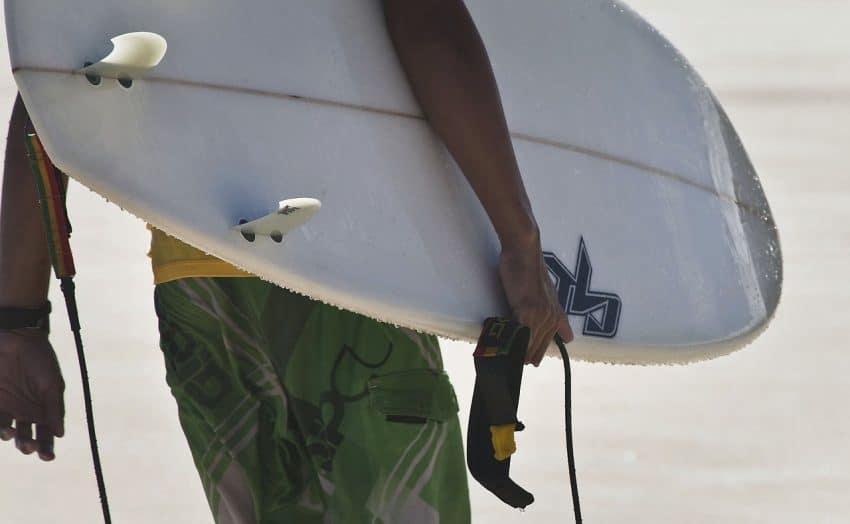 Imagem mostra braço de um homem segurando uma prancha de surfe, mostrando detalhes como as quilhas e o leash (cordinha).
