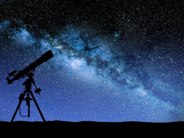 Um telescópio montado a noite com o céu estrelado em tons.