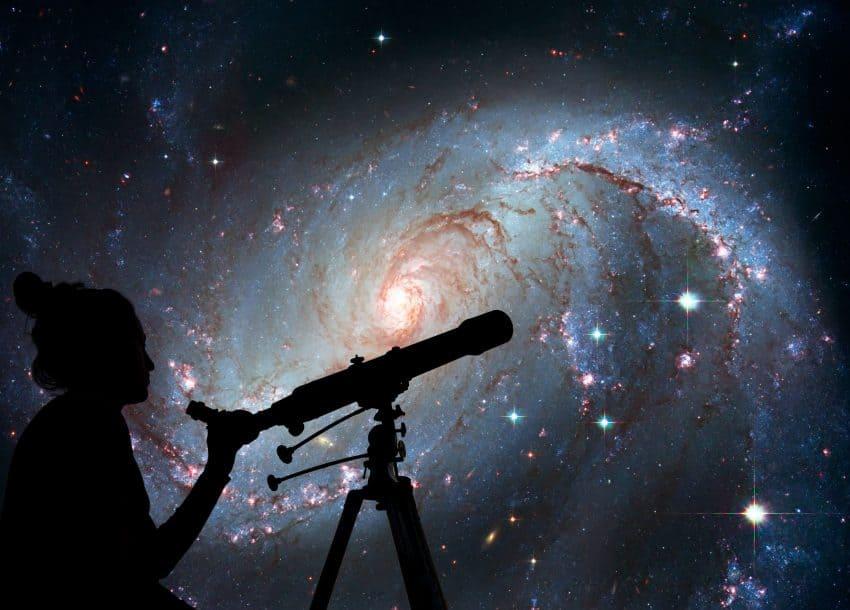 Imagem da sombra de uma mulher e um telescópio com o céu ao fundo.