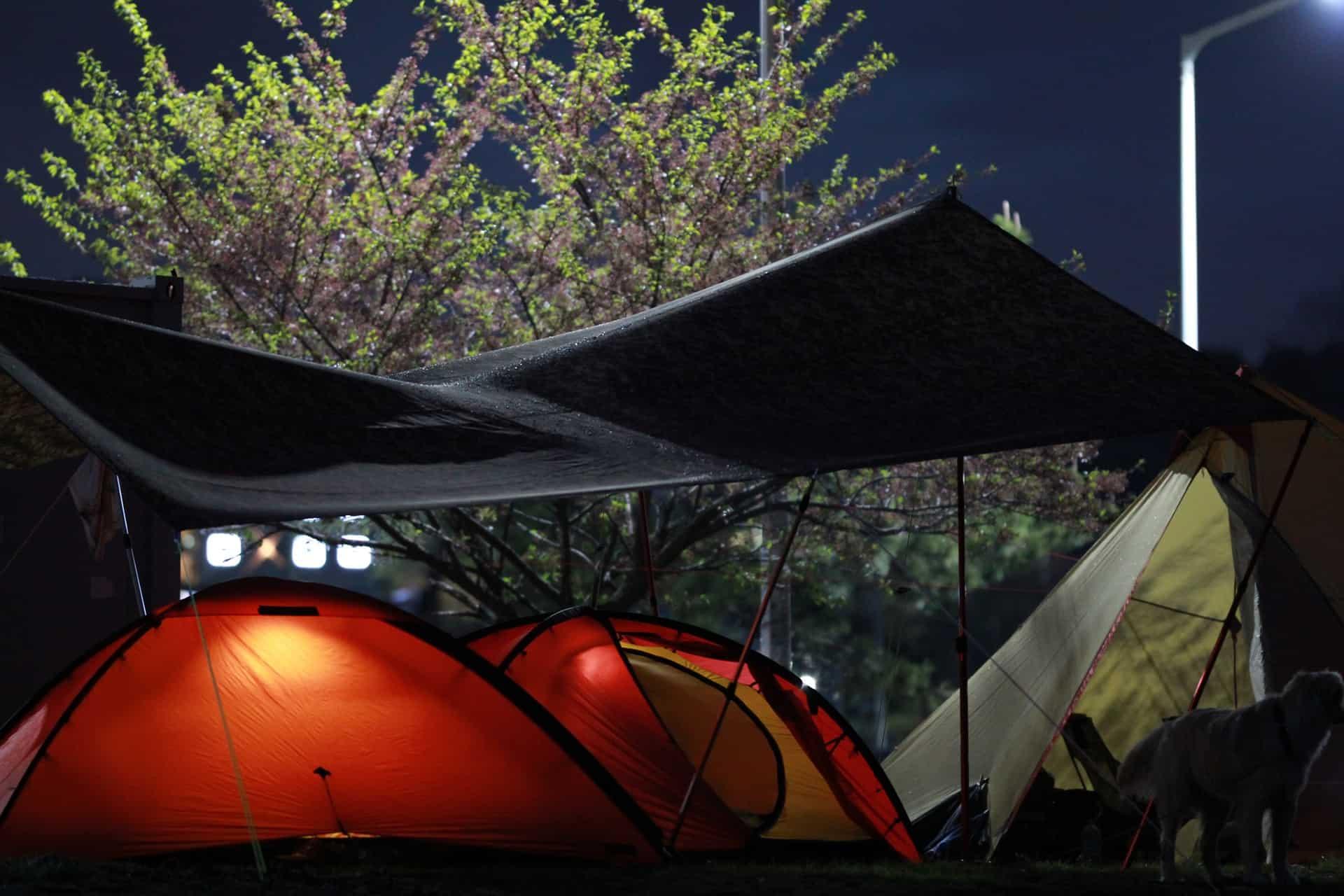 Imagem de uma tenda cobrindo algumas barracas em um acampamento.