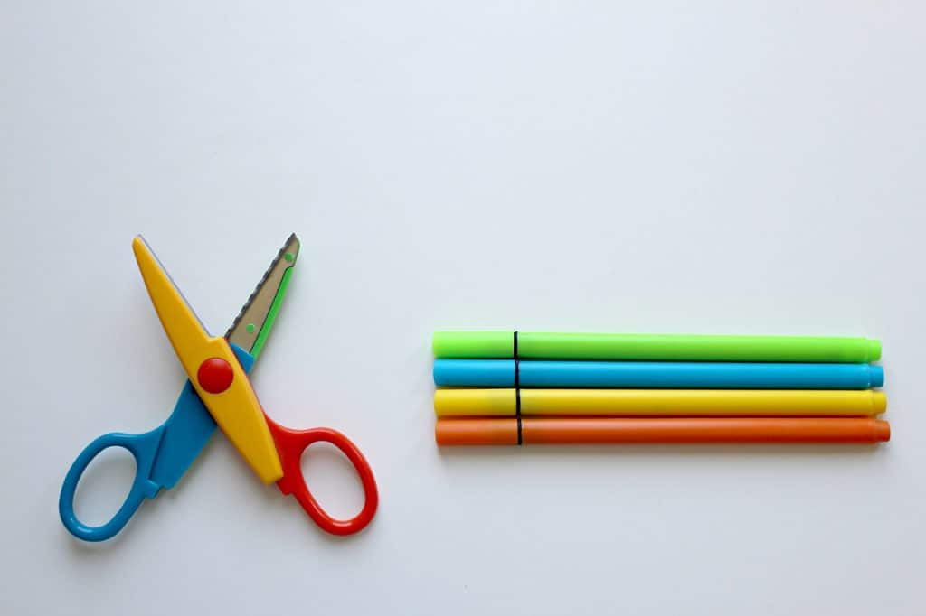 Imagem mostra um tesoura escolar colorida aberta ao lado de quatro canetinhas.