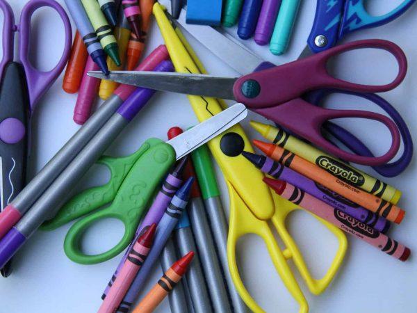 Imagem mostra diversas tesouras escolares em meio a materiais como gizes de cera e canetinhas coloridas.