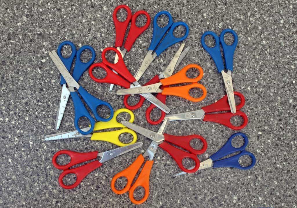 Imagem mostra muitas tesouras escolares coloridas.