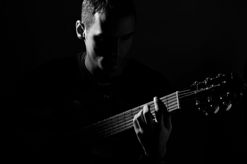 Silhouette of man playing guitar.