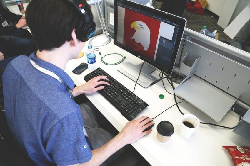 Homem sentado em frente a uma escrivaninha branca tratando uma imagem em um computador.