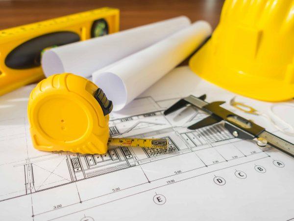 Imagem de uma trena sobre a mesa ao lado de outros instrumentos de construção.