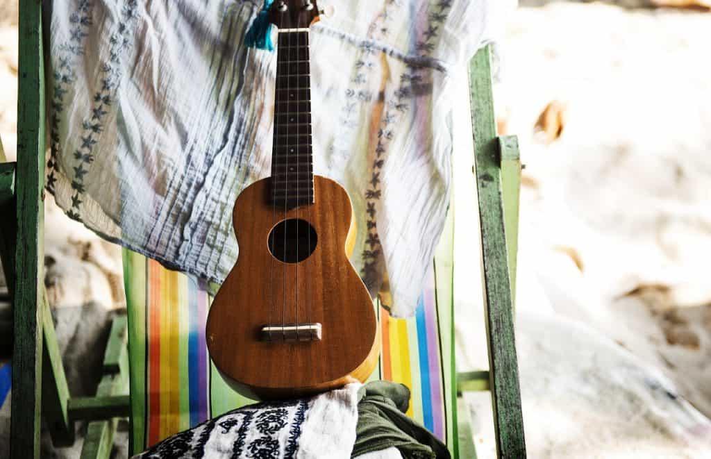 Imagem mostra ukulele sobre cadeira e panos.