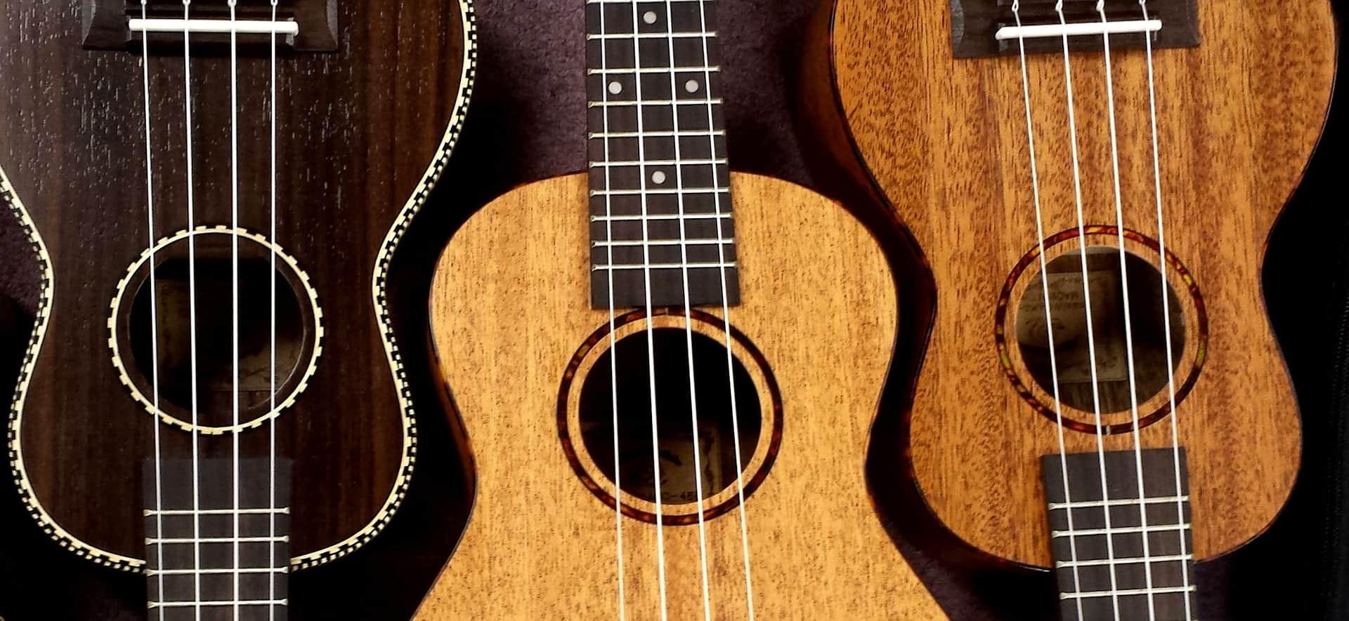 Imagem mostra três ukuleles de cores diferentes feitos de madeira um ao lado do outro.