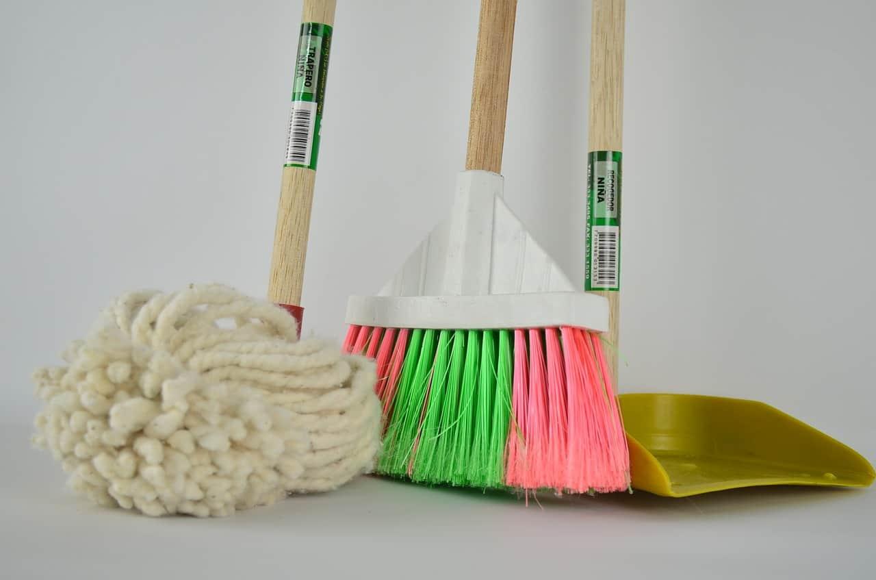 Esfregão branco, vassoura verde e rosa e pá de lixo em um fundo branco.