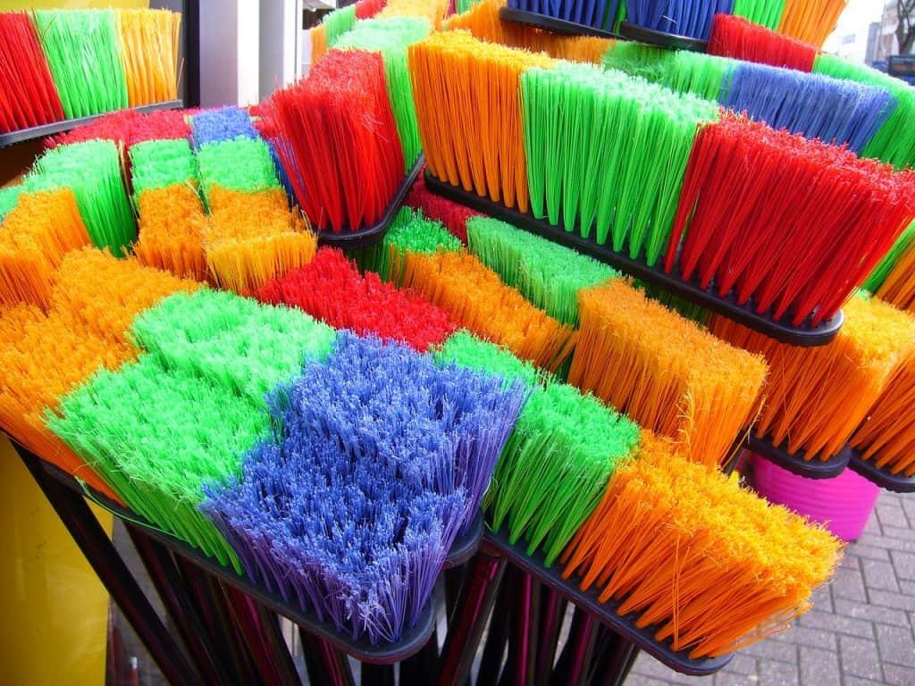 Zoom nas cerdas de diversas vassouras coloridas.