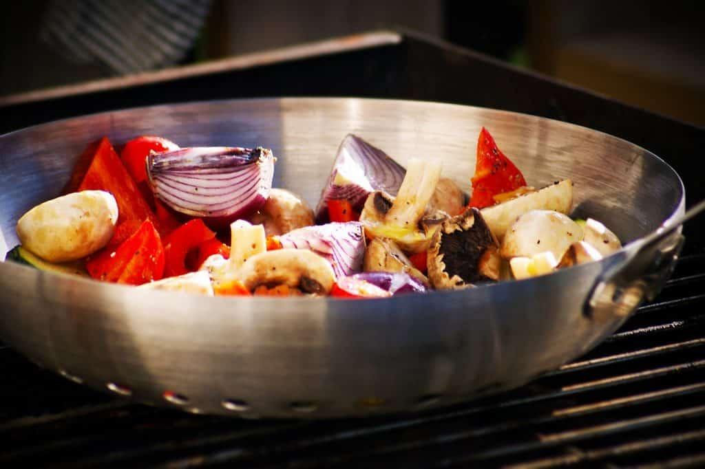 Cebolas, cogumelos e tomates em pedaços grandes dentro de panela wok de aço.