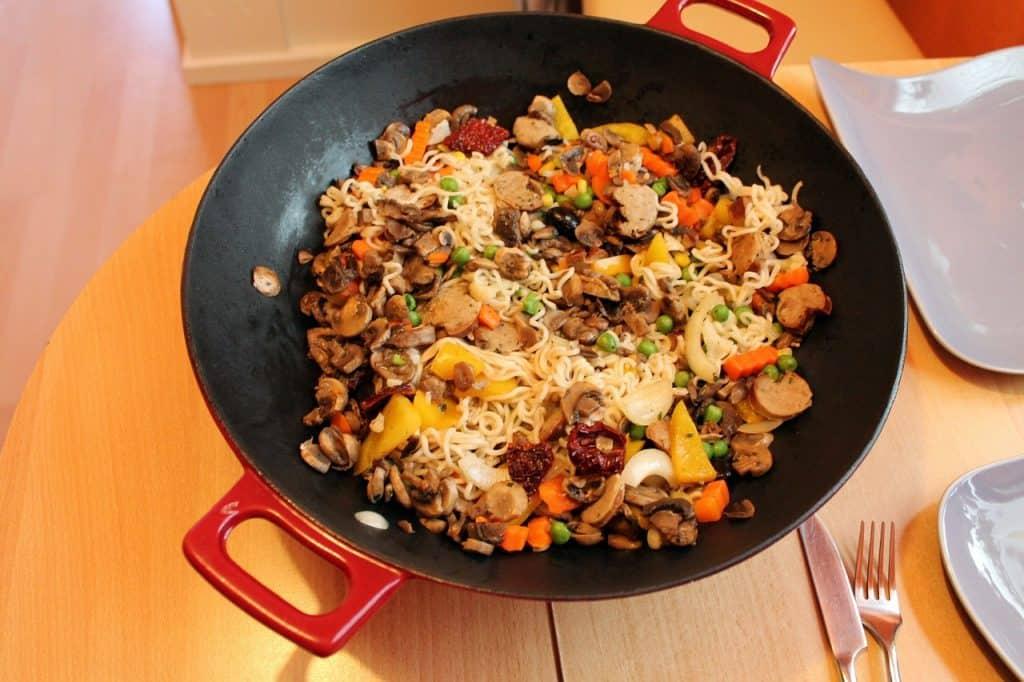 Panela wok sobre a mesa com refogado de legumes e macarrão.