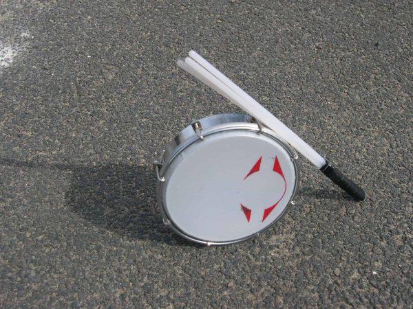 Imagem de um tamborim sobre o chão e uma baqueta tripla apoiada no instrumento.