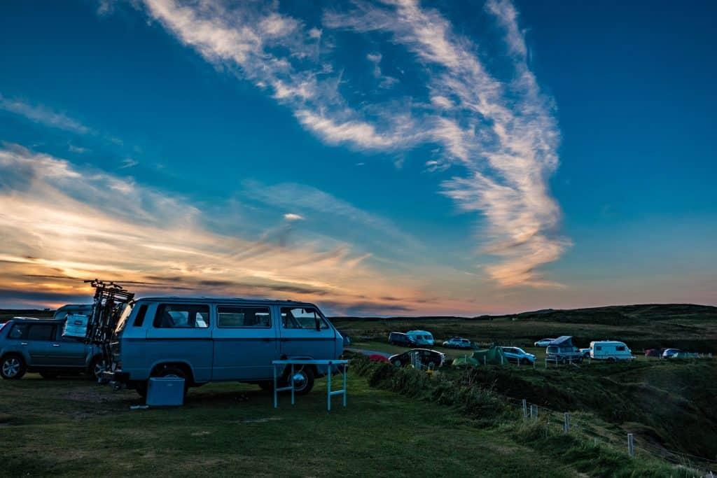 Imagem de camping com carros e trailers estacionados e barracas de acampamento armadas.