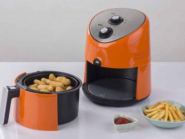 Imagem de airfryer laranja sobre mesa com bolinhos dentro e batatas ao lado.
