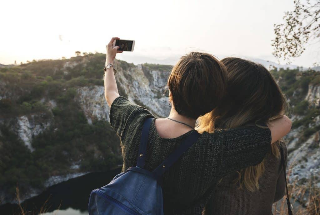 Imagem mostra duas amigas de costas tirando selfie e uma paisagem de montanhas à frente.