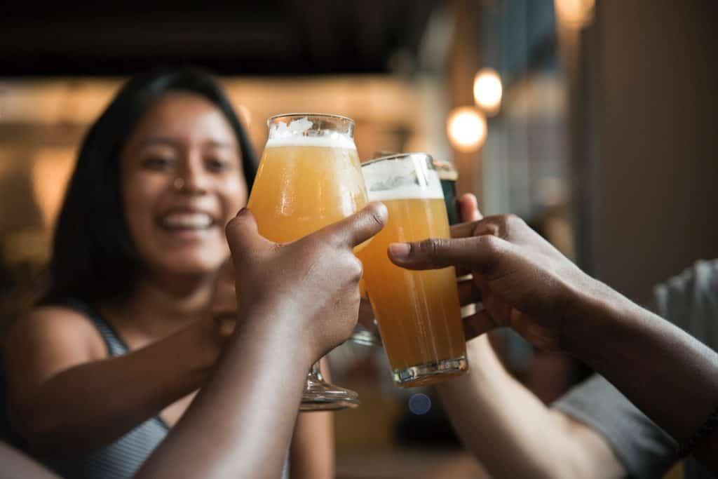 Foto de um grupo de amigos brindando com diferentes copos de cerveja.
