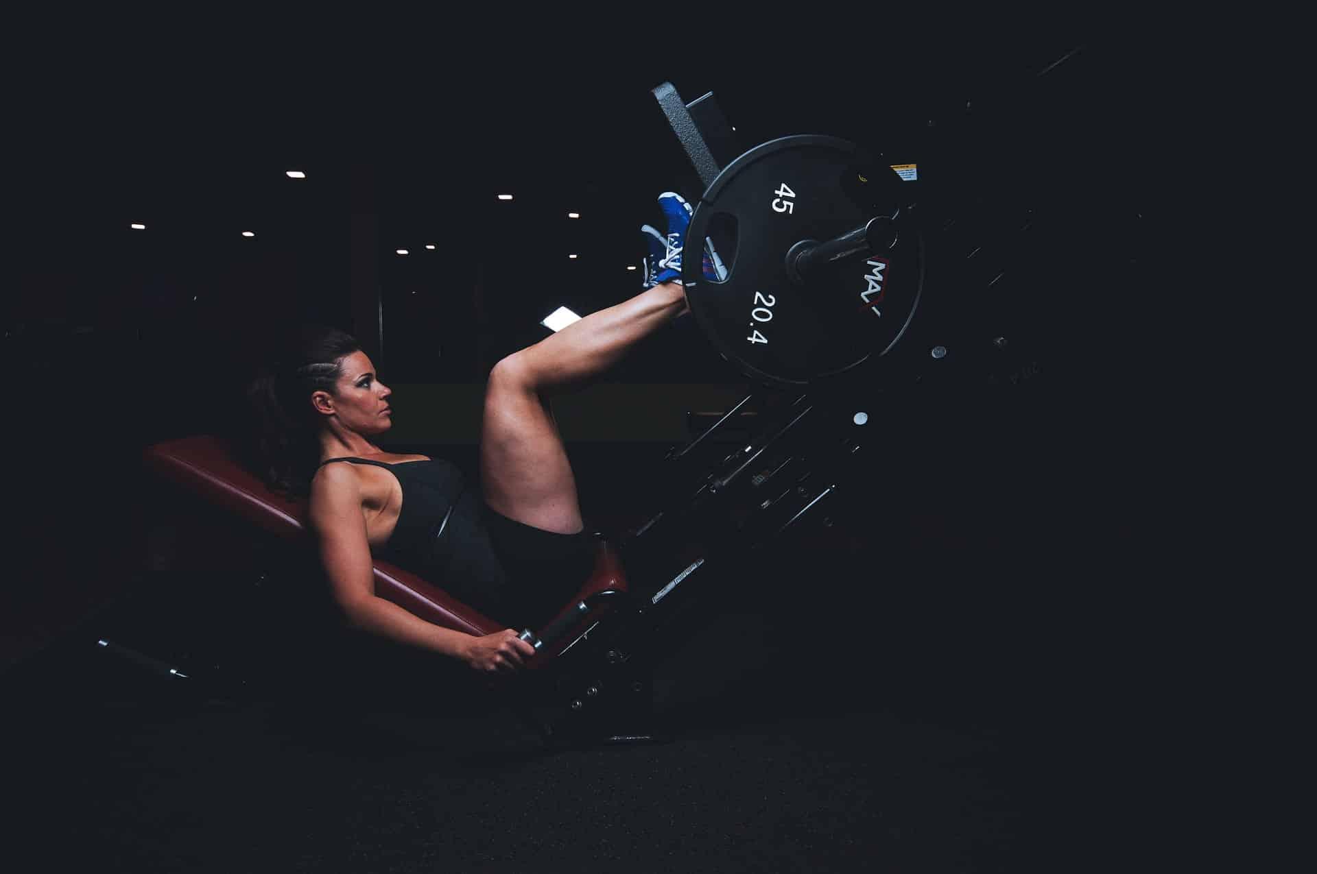 Imagem de mulher fazendo exercício para as pernas em aparelho de ginástica.