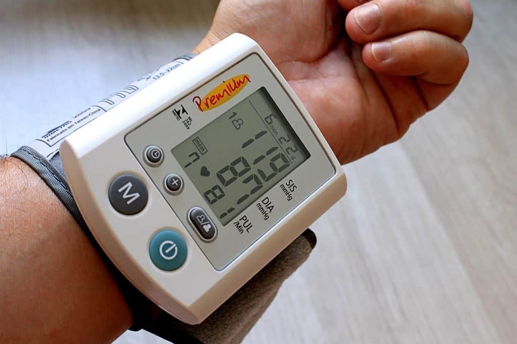 A imagem mostra um braço e uma mão com um medidor de pressão digital no pulso.