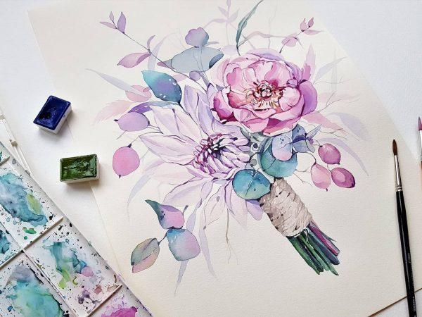 Na foto um ramalhete de flores pintado com aquarela em uma folha de papel com dois pincéis do lado direito e uma cartela de tintas do lado esquerdo.