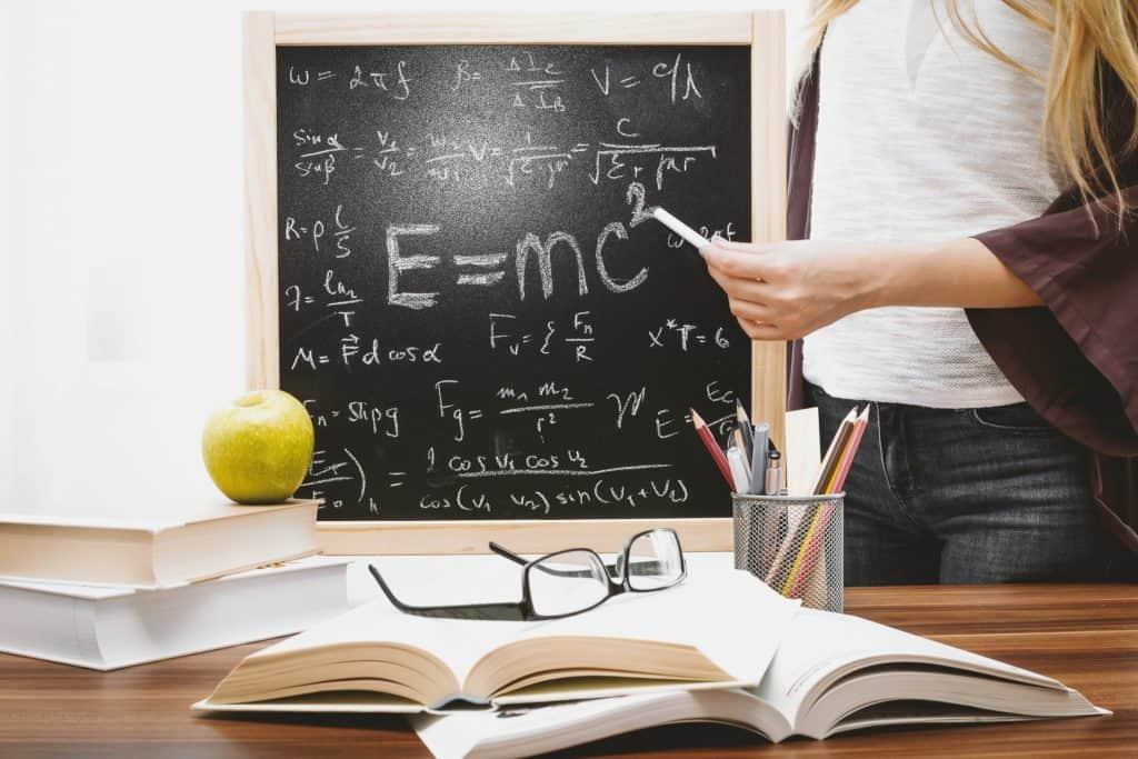 Imagem de pessoa segurando giz com quadro com informações de matemática.