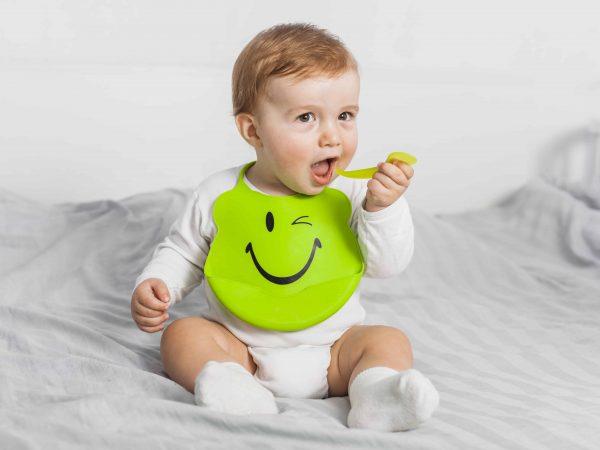 Bebê de branco sentado usando babador verde.