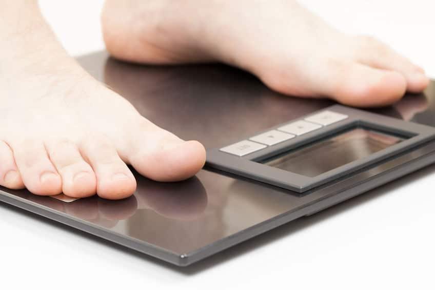 Imagem mostra os pés de uma pessoa sobre uma balança digital.