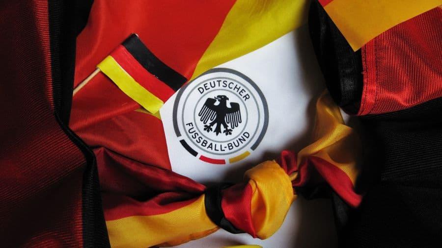 Imagem mostra o símbolo da Federação Alemã de Futebol estampada numa camisa. Mangas de camisetas, tecidos e até uma pulseira ficam ao seu redor, como uma moldura.