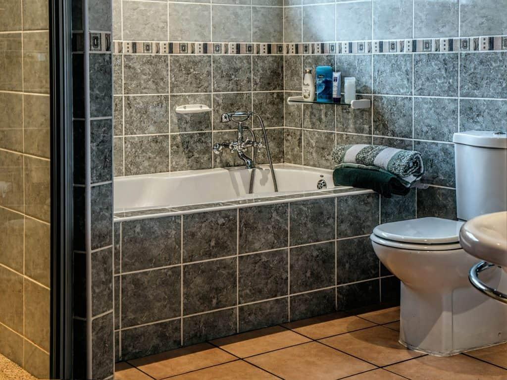 Imagem de banheiro em tons de cinza com toalhas coloridas na beira da banheira.
