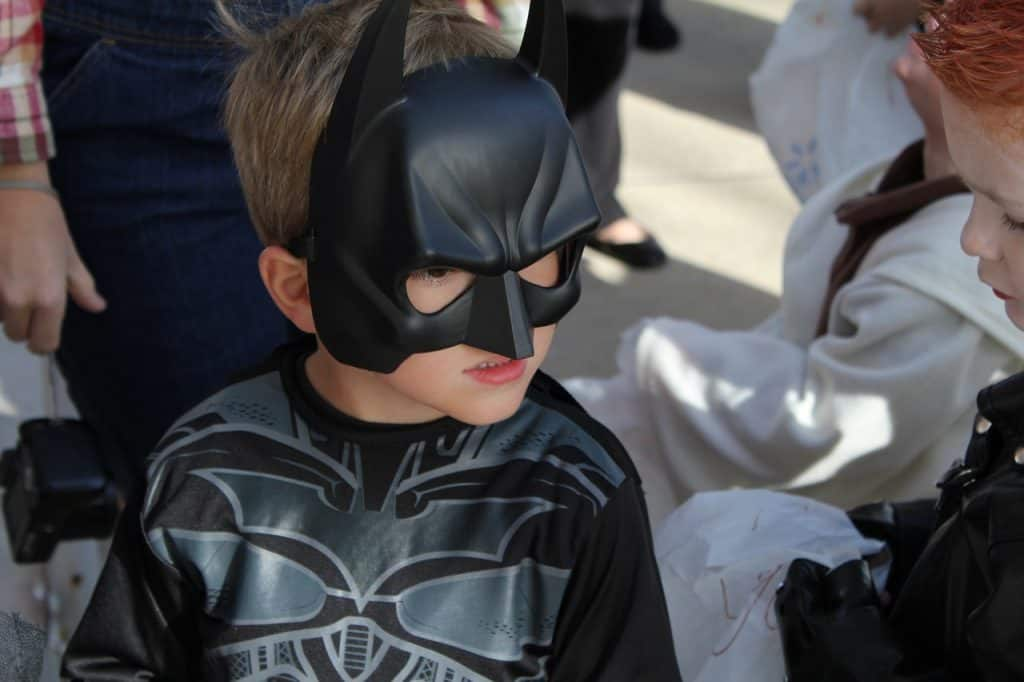 Na foto um menino com fantasia do Batman.