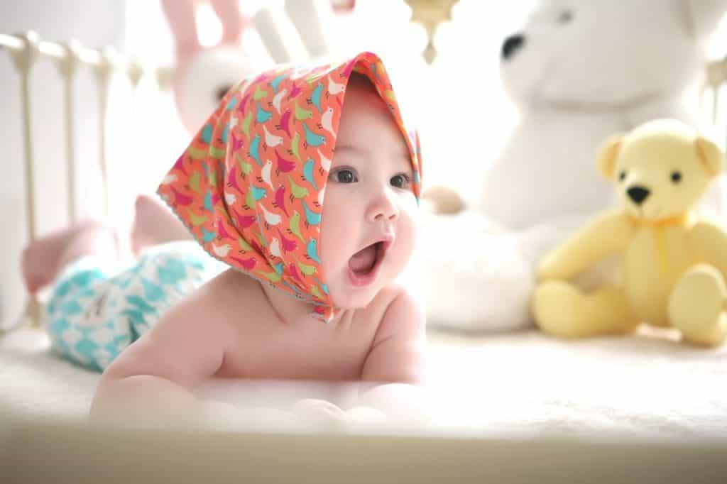 Na foto um bebê deitado de bruços em um berço.