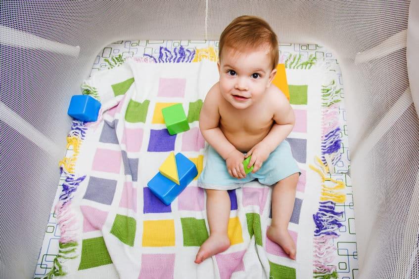Imagem de bebê brincando dentro de cercado.