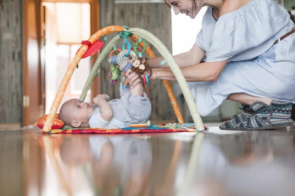 Mulher brinca com bebê deitado em tapete de atividades.