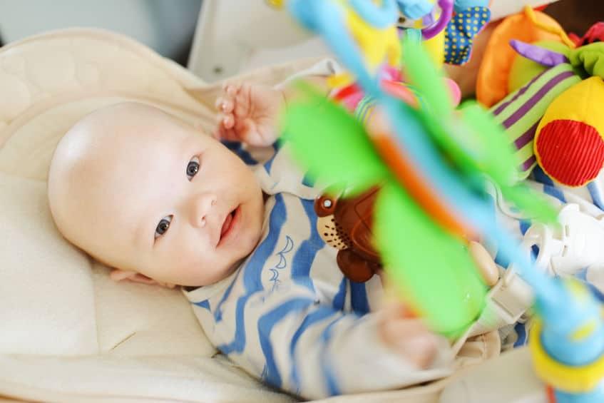Imagem de bebê brincando com móbile de cadeirinha de descanso.