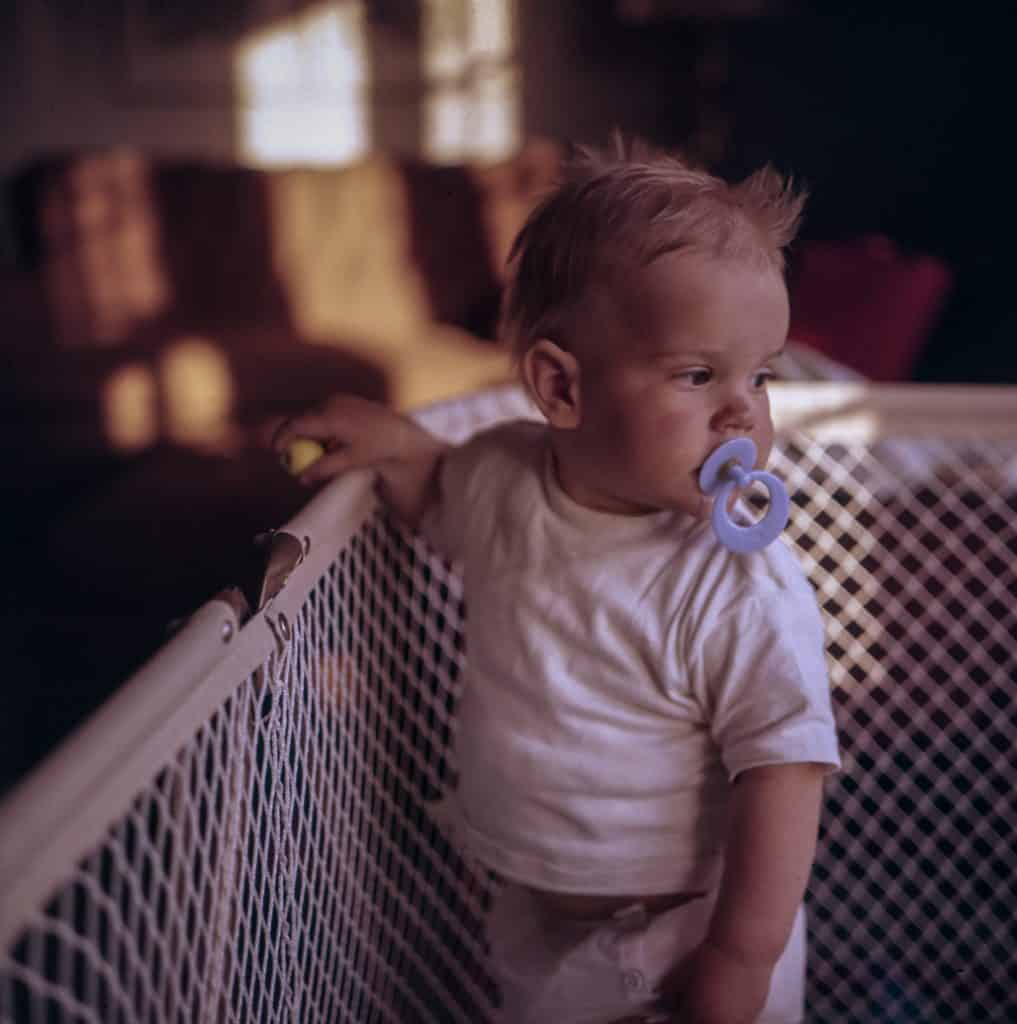 Image of a baby standing inside a playpen.