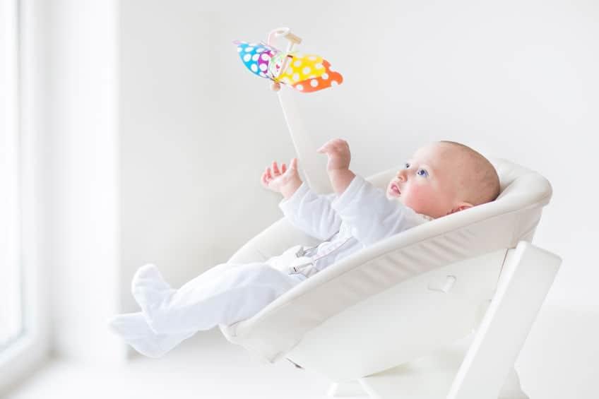 Na foto um bebê dormindo em uma cadeira de balanço.