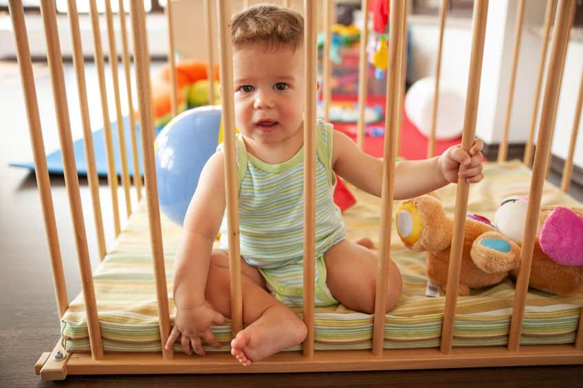 Imagem de criança dentro de cercado.