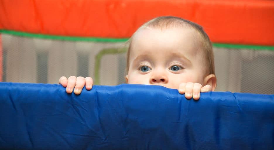 Imagem de bebê espiando sobre cercado.