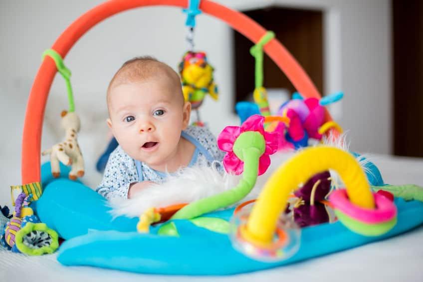 Imagem de bebê em tapete de atividades.