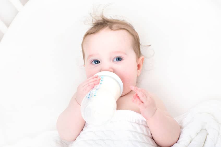 Image of baby sucking milk and holding bottle.