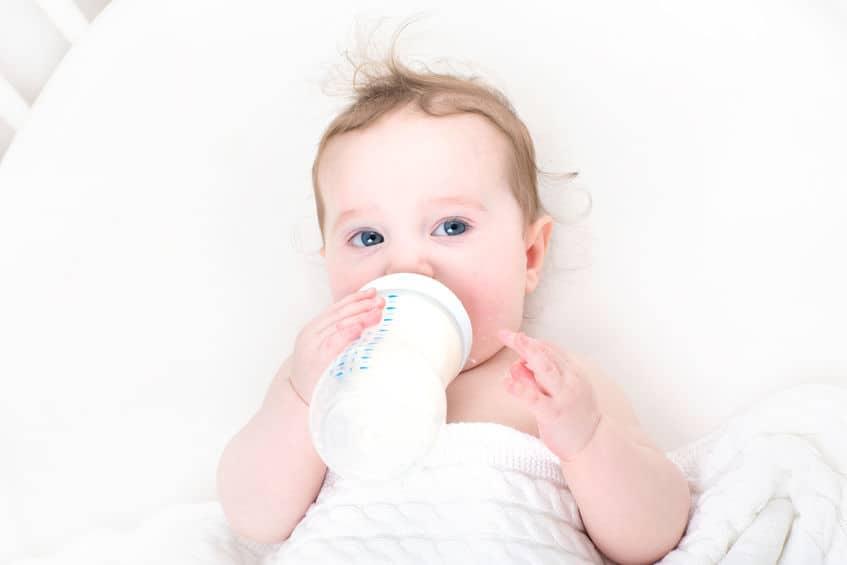 Imagem de bebê mamando leite e segurando mamadeira.