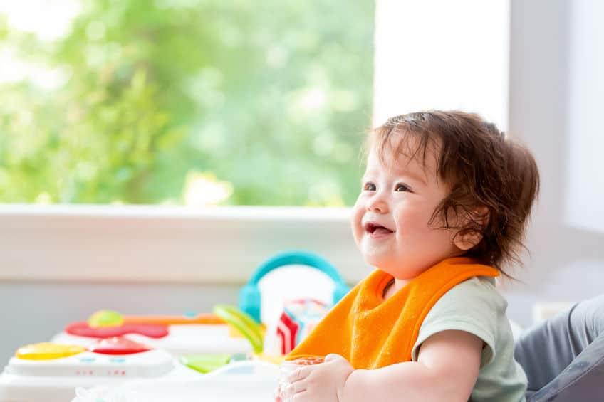 Criança com babador laranja sentada na cadeirinha e sorrindo.