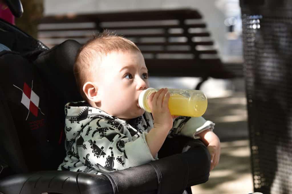 Imagem de uma criança tomando suco em uma mamadeira