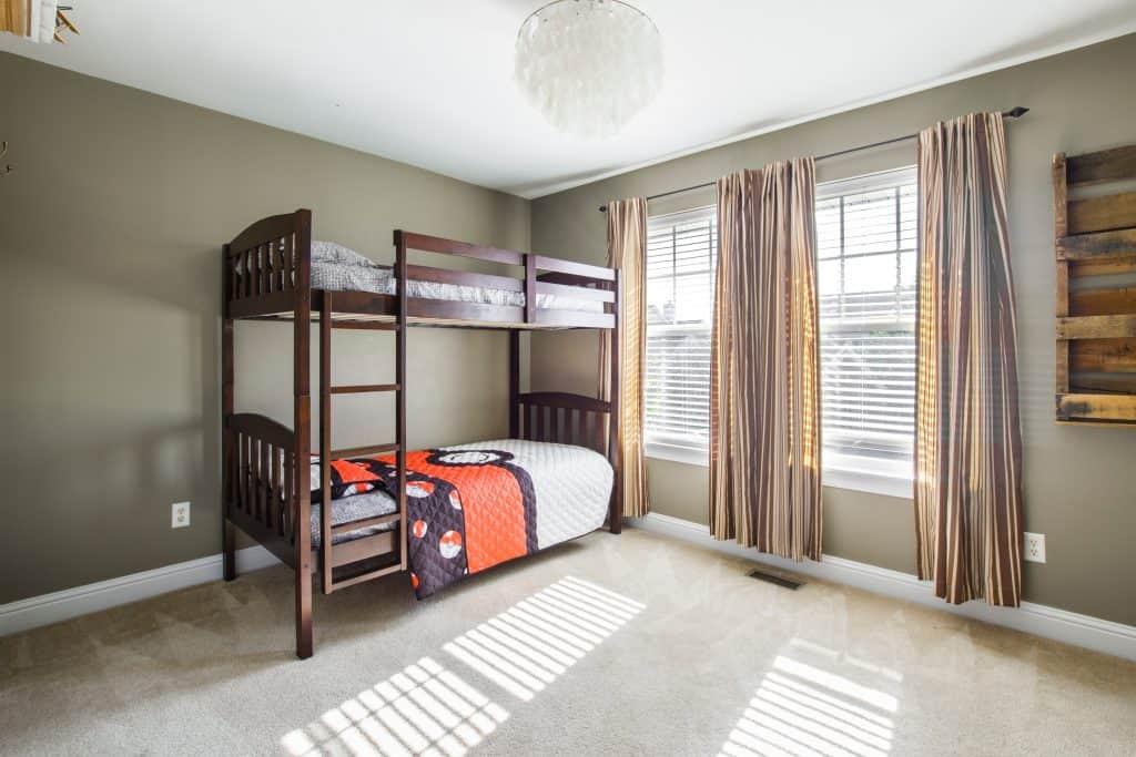 Foto de uma cama beliche de madeira escura, básica, em um quarto com paredes, piso e cortinas em tons pastéis.