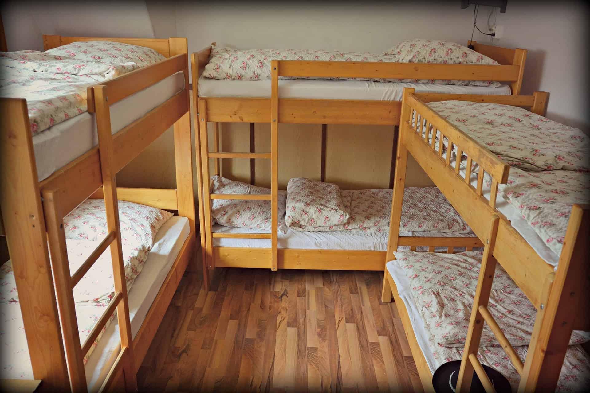 Foto de três beliches juntas em um cômodo, feitas de madeira clara, com roupa de cama floral.